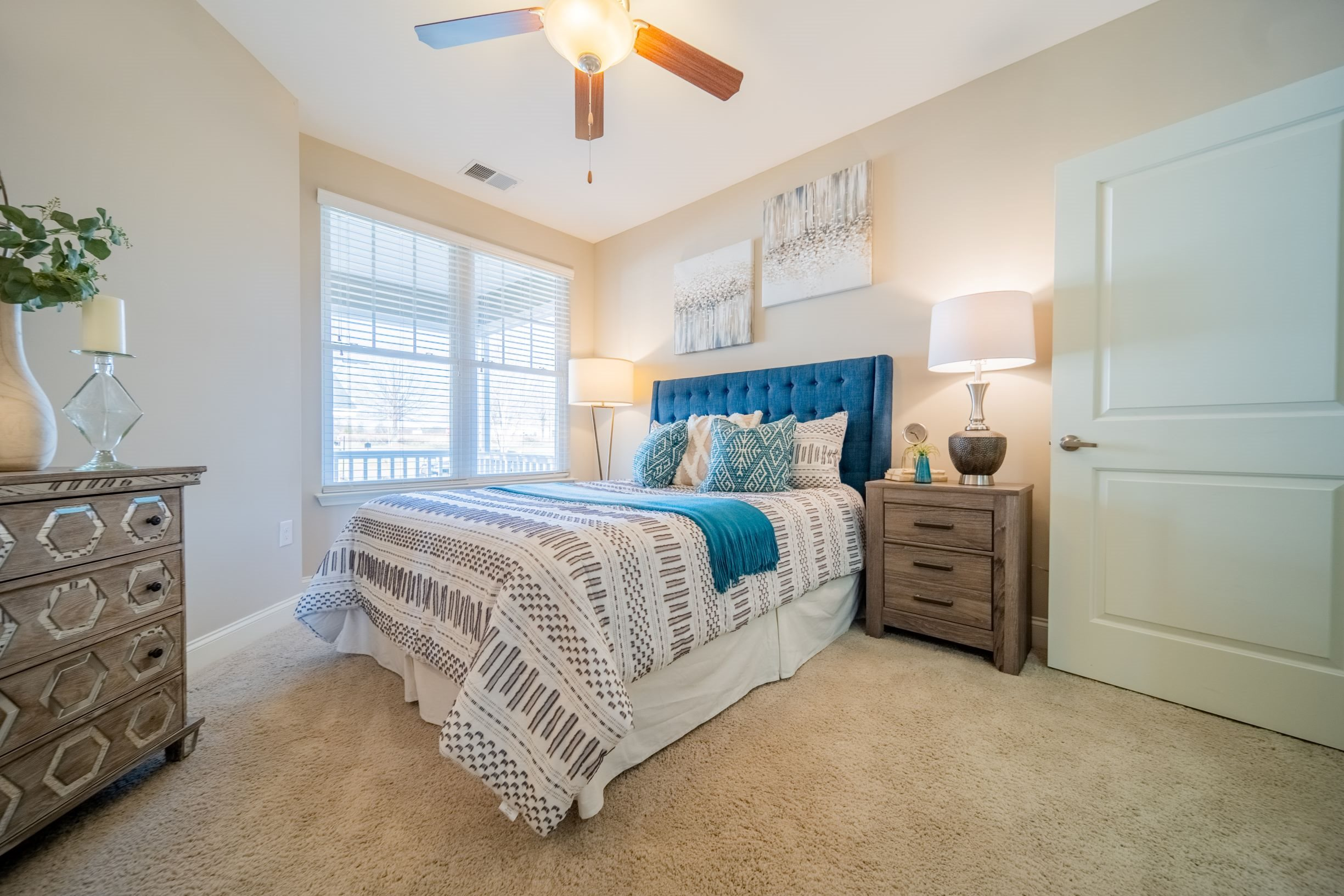 Beautiful bedroom with plush carpeting, lighted ceiling fan and oversized window at Piedmont Place in Greensboro, NC
