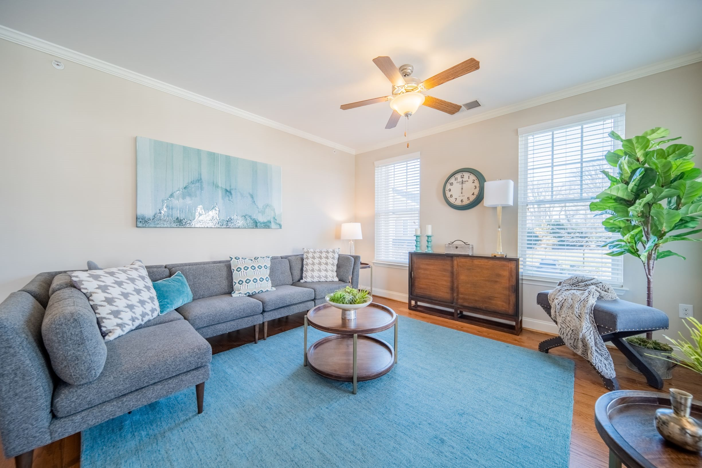 Spacious living room with lighted ceiling fan and hardwood style flooring at Piedmont Place in Greensboro, NC