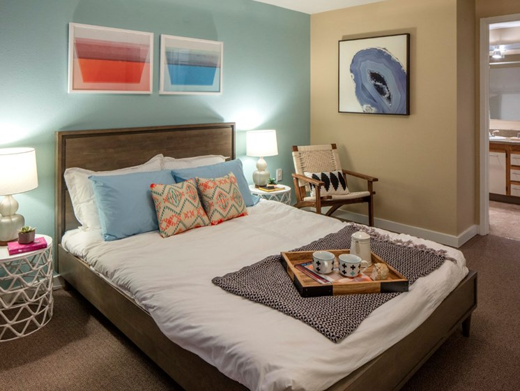 Spacious bedroom with carpeting and private bathroom at Landmark at Tanasbourne Apartments in Hillsboro, OR 97124