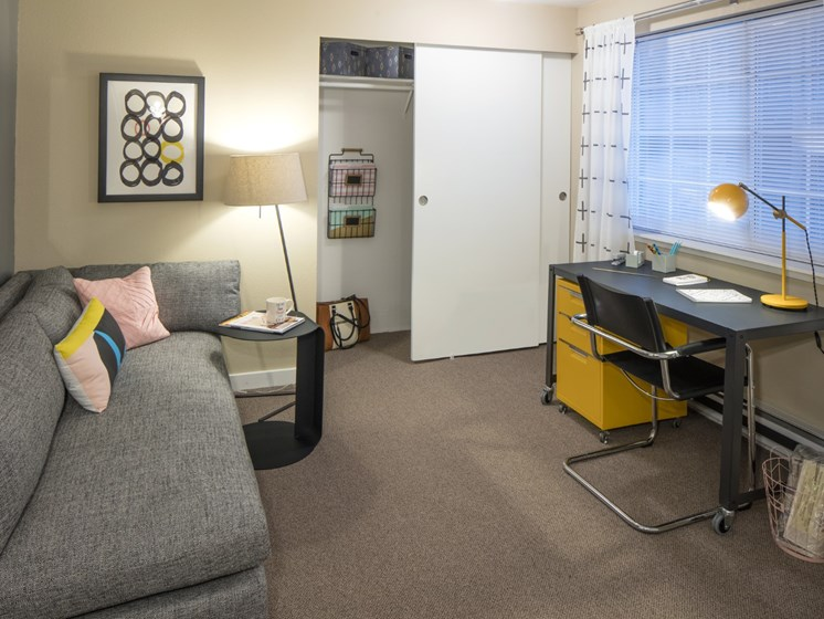 Extra room made into den with study desk, sofa, closet, and carpeting at Landmark at Tanasbourne Apartments in Hillsboro, OR 97124