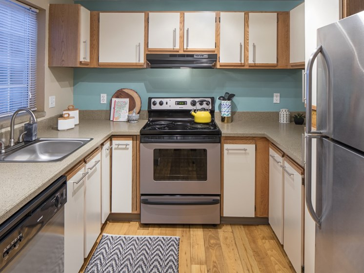 Kitchen with stainless steel appliances and wood flooring at Landmark at Tanasbourne Apartments in Hillsboro, OR 97124