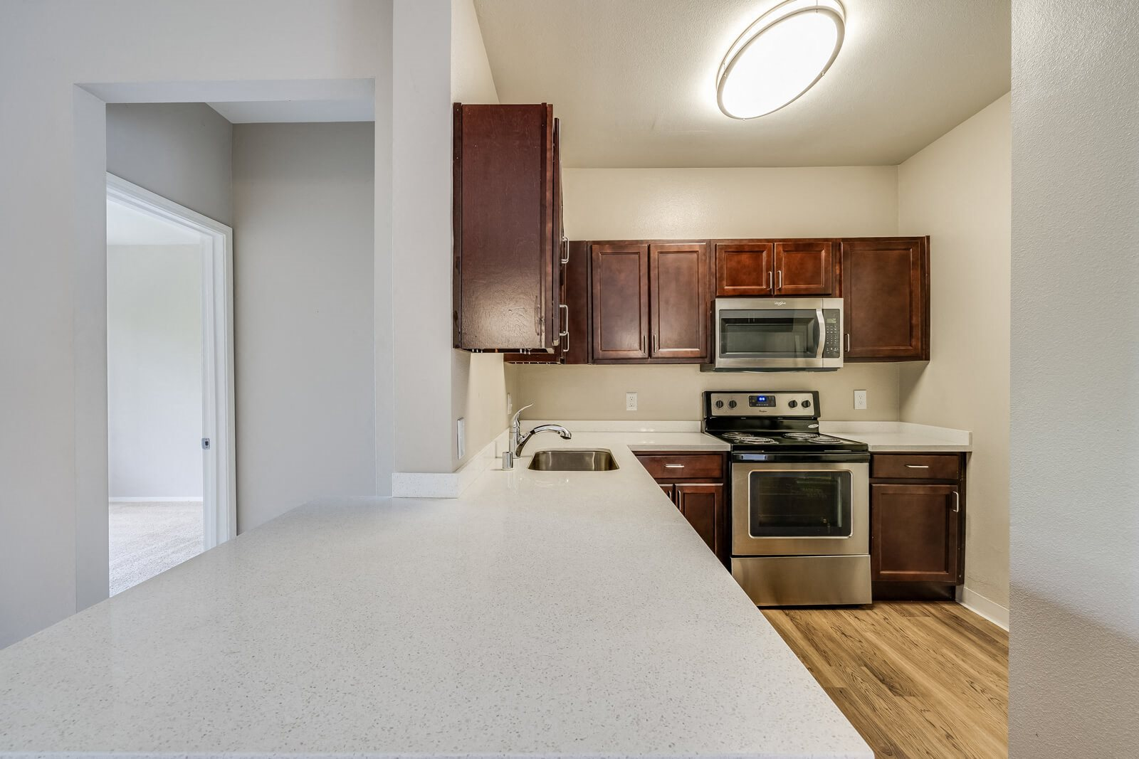 White Quartz Counter With Custom Cabinetry In Kitchen at Pavona Apartments, 95112, CA