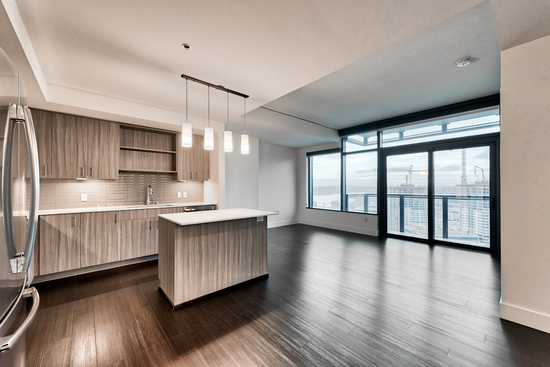 Wood plank flooring throughout the open layouts create a flexible living space at Cirrus, Seattle, Washington