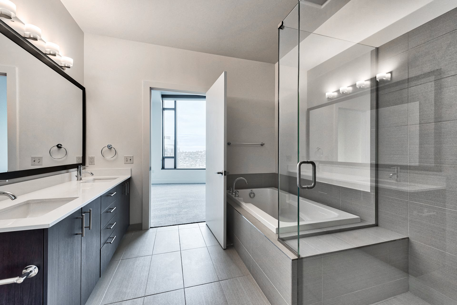 Spa inspired bathroom with glass shower, soaking tub and dual vanity at Cirrus, Seattle, Washington.