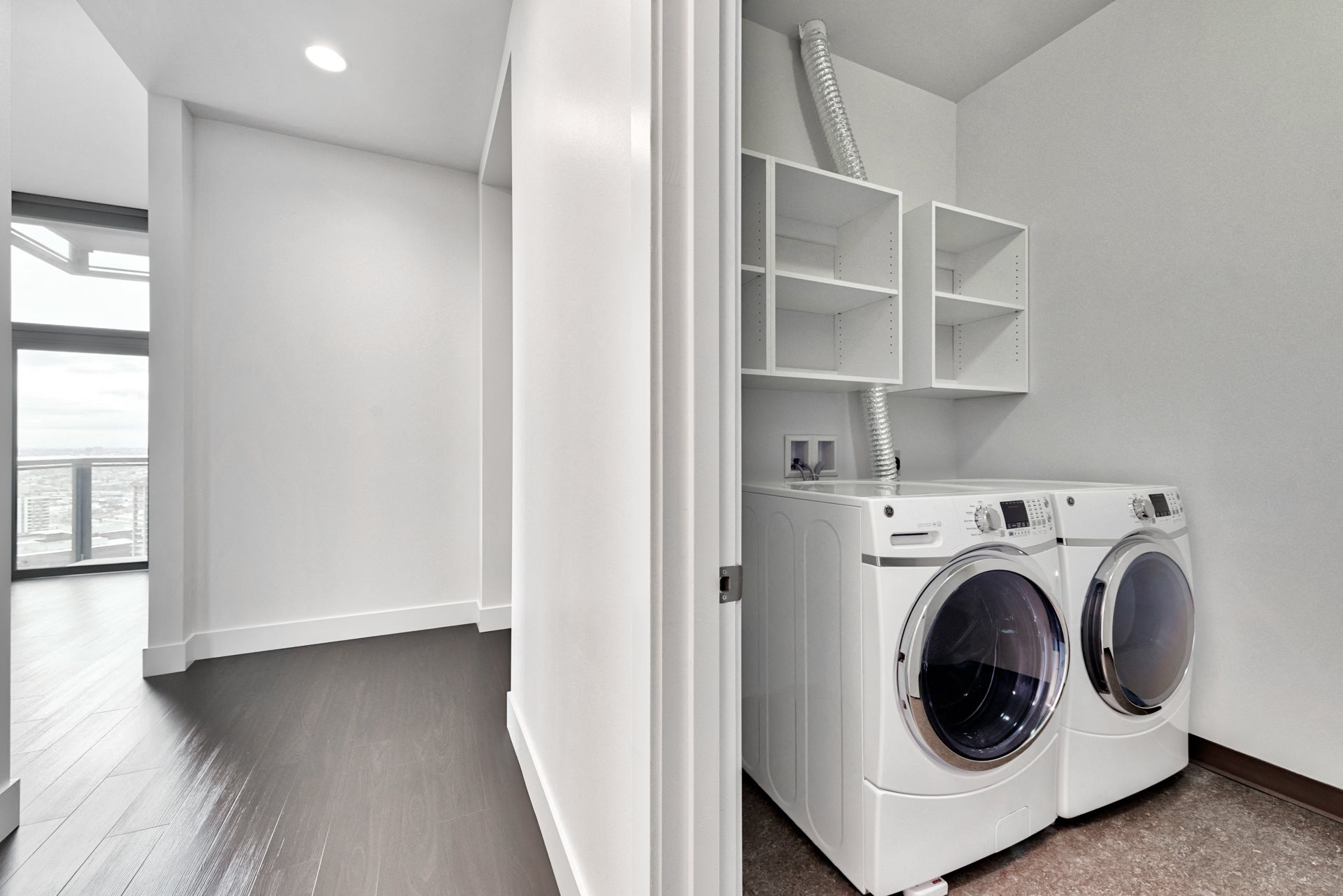 Laundry rooms with front loading side-by-side washer and dryers at Cirrus, Seattle, Washington