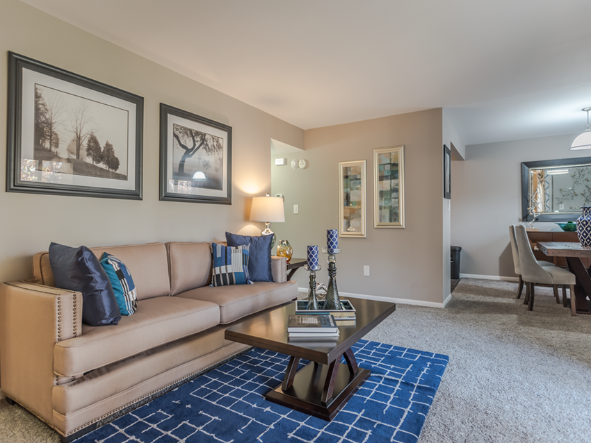 Towson MD apartment living room at Versailles apartments with couch, coffee table, framed wall art and rug