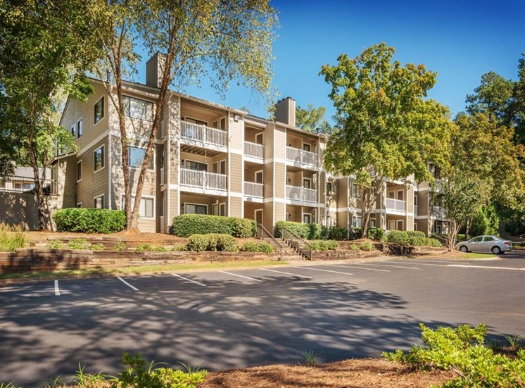 Meticulously maintained grounds with mature trees surround the soft neutral paint and brick exterior apartment homes at Rosemont Apartments, Roswell, GA 30076