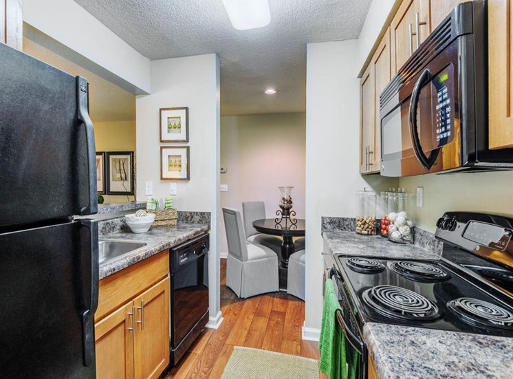 Gourmet Kitchens with G.E. Black Appliances and Maple Raised-Panel Cabinetry at Rosemont Apartments, Roswell, GA 30076