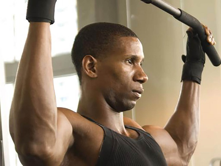 man using exercising machine at fitness center_Northpark at Scott Carver Apartments Miami, FL