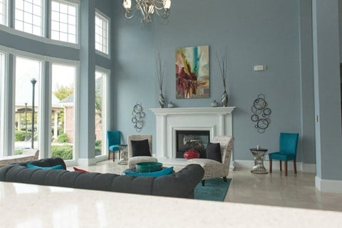 Community club house with large blue couch, white fireplace, blue arm chairs, large windows and photos hung on wall above and around the fireplace.