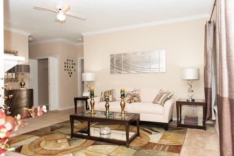 Living room with large white couch, side tables with lamps, coffee table, large area rug and a hanging  ceiling fan.