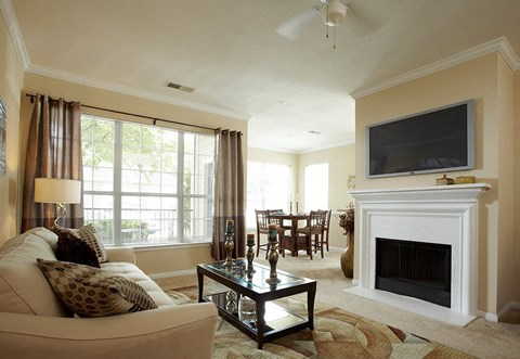 Livingroom with large white couch, side table with lamp, large window with curtains, coffee table, area rug, hung ceiling fan, and TV hung over white fireplace.