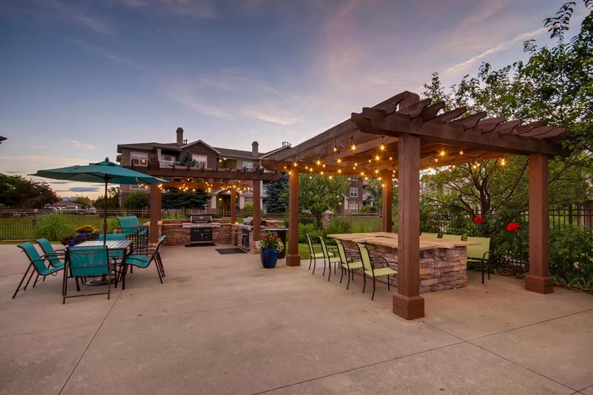 Dusk photo of a pergola with market lights, seating area and a table with chairs & an umbrella to the left.