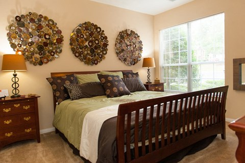 Bedroom with dark wood bed, dark brown side tables, large wood decor on the wall and greenish brown colored bedding.