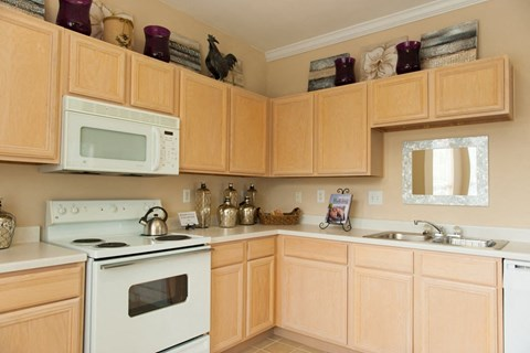 Kitchen with white appliances, light tan color cabinets and light tan colored counter top.