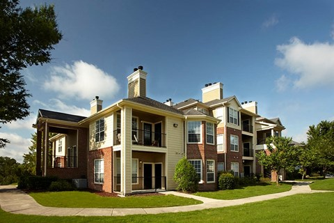 Exterior image of an Apartment Building with green space and clouds in the background