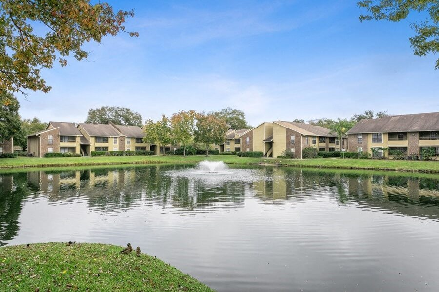 Large pond/lake showcasing exterior of apartment buildings and beautiful landscape