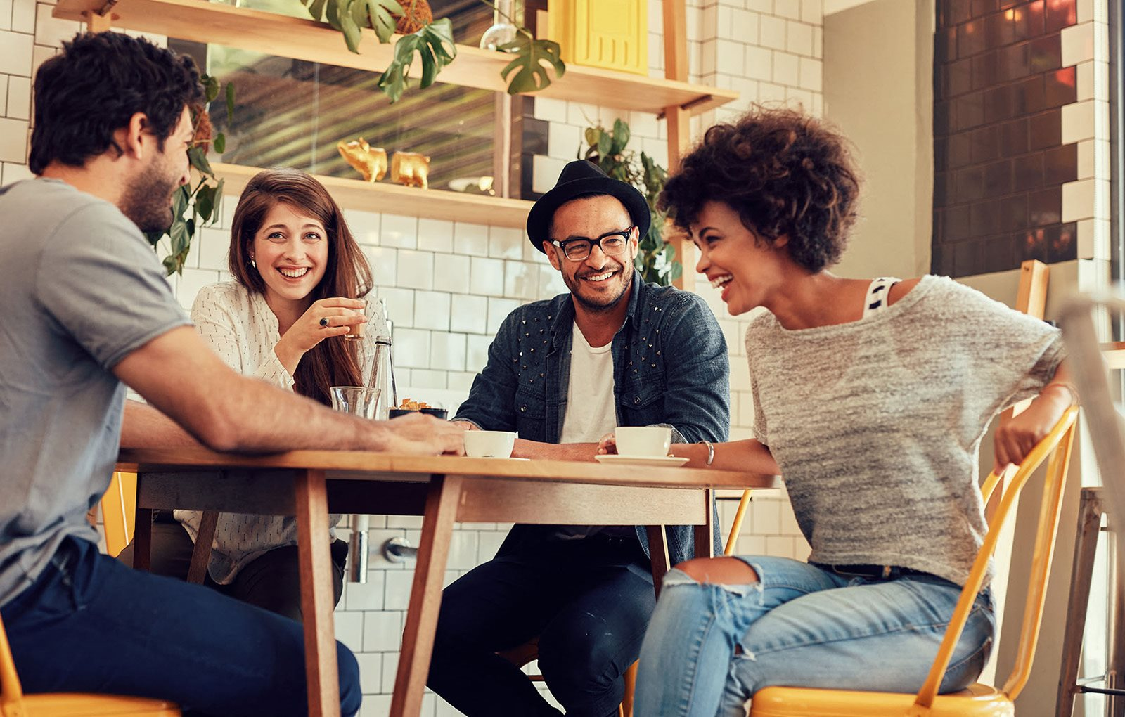 Four people sitting around a table happily chatting