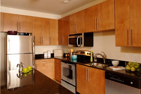 Kitchen with oven, dark counters, light cabinets, microwave, sink and refrigerator