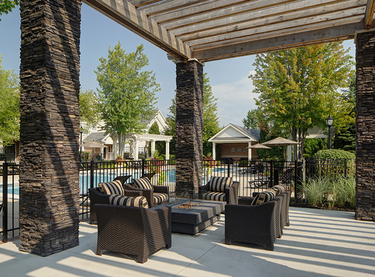 Pergola Covered Outdoor Lounge Next to Pool with Fire Pit