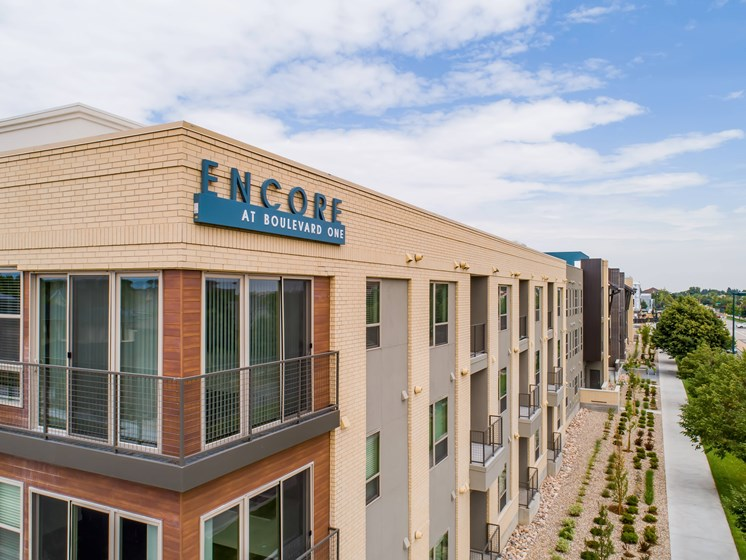 Elegant wood and white brick exterior at Encore Boulevard One Apartments, 7108 E Lowry Boulevard, CO