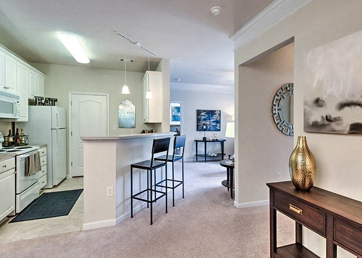Kitchen with white appliance package and tile floors at Abberly Green Apartment Homes by HHHunt, Mooresville, NC 28117