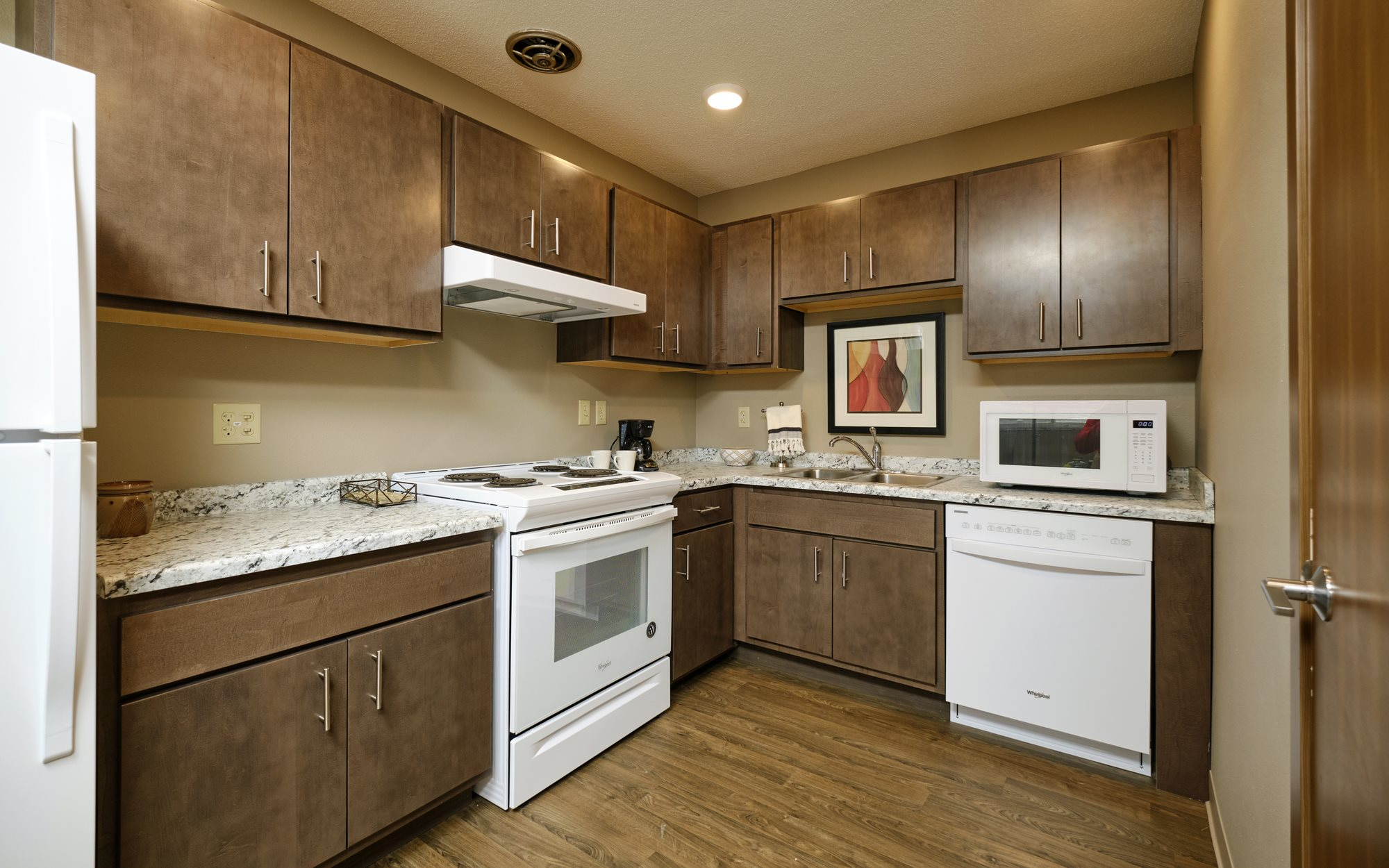 A kitchen in Sunset Apartments shows all appliances including microwave and dishwasher are included.