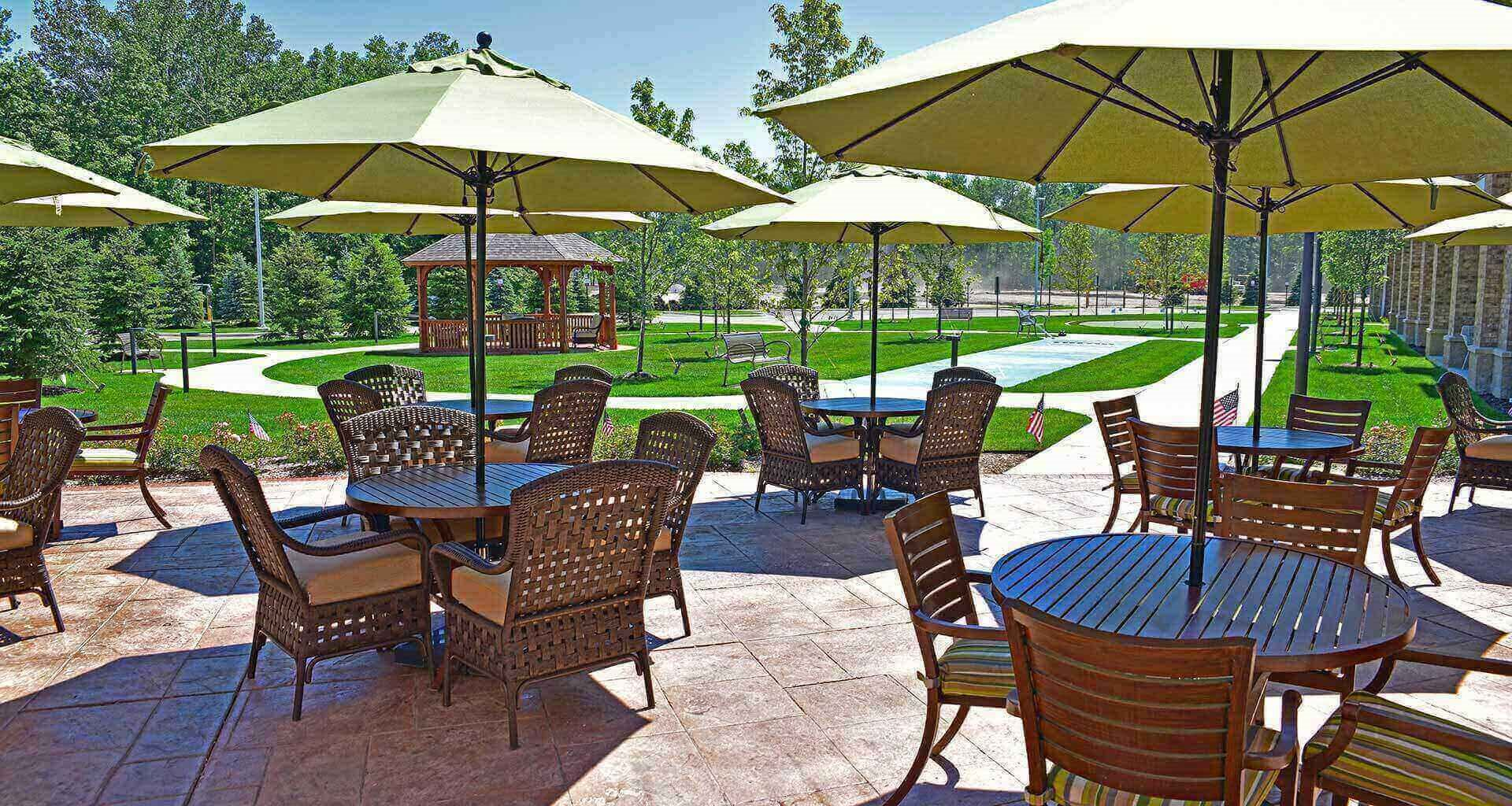 Umbrella Shaded Chairs In Courtyard at Rose Senior Living – Avon, Avon