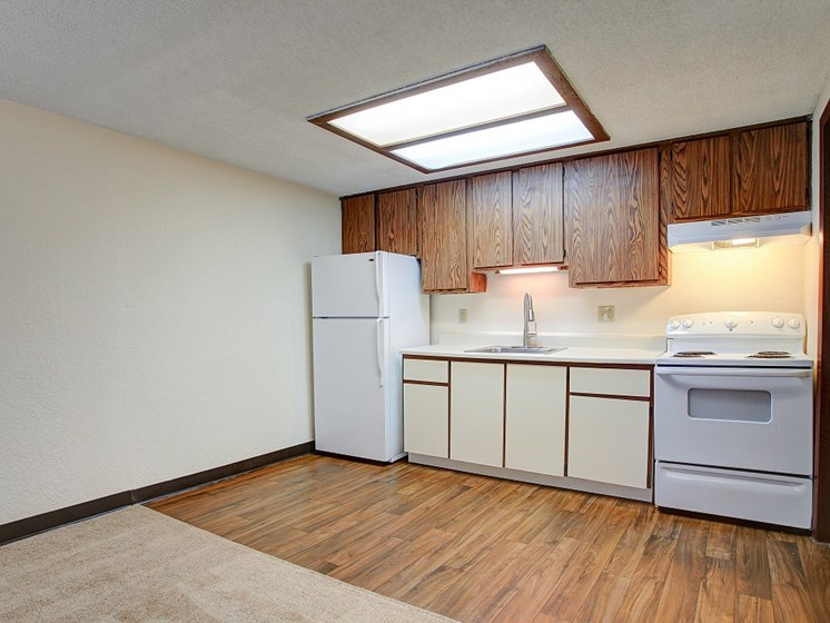Kitchen area with vinyl flooring and white appliances