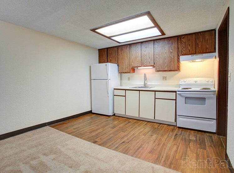 Kitchen area with vinyl flooring and wood cabinets