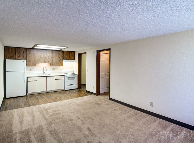 Living room with plush carpeting leading to kitchen