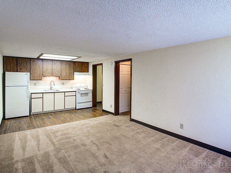 Living room with plush carpeting leading to kitchen area