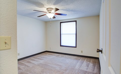 Bedroom with plush carpeting, a large window, and a ceiling fan.