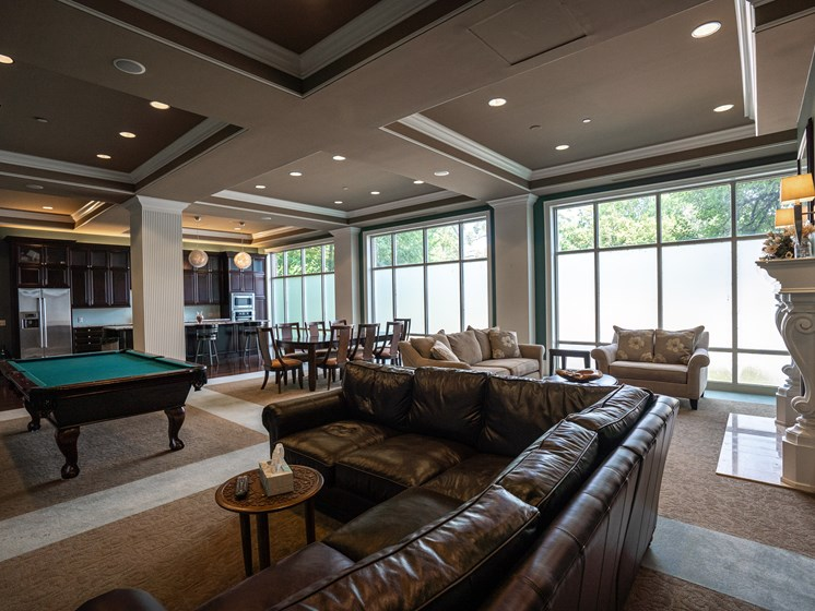 Club room at Residences of Creekside with brown leather couches and pool table.