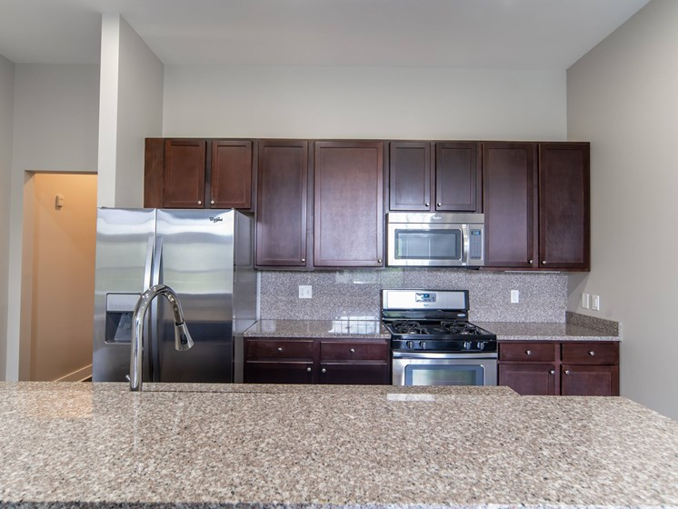 Kitchen with dark cherry cabinets, granite counter tops, and stainless steal appliances.
