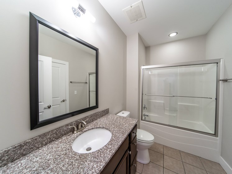 Bathroom with large mirror. Updated granite vanity with sink, toilet, and shower tub combo.