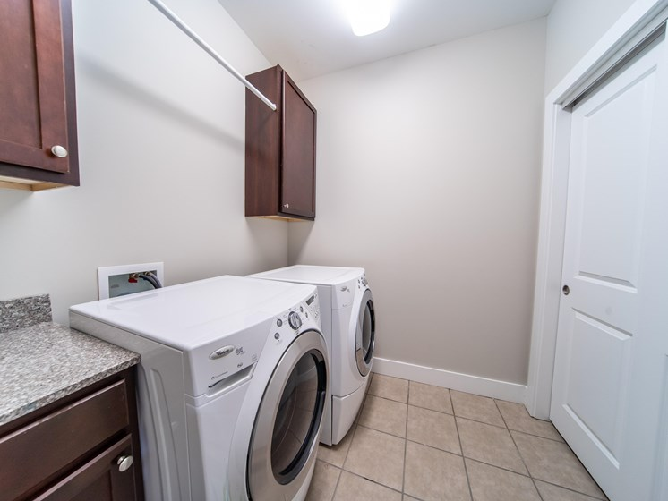 Laundry room with tile floors, washer and dryer, cabinets, and hanging rack.
