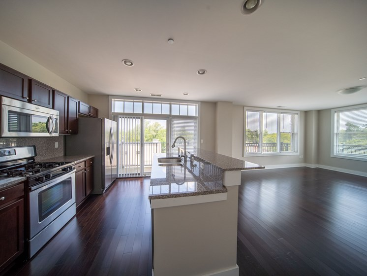 Modern kitchen with large windows, stainless steal appliances, and a large kitchen island at the Residences of Creekside.
