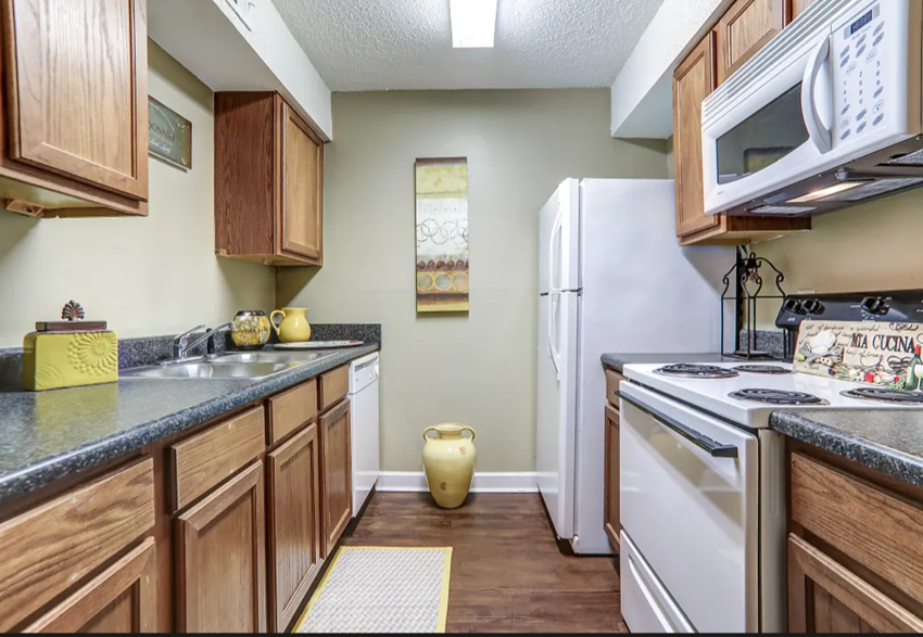 Kitchen with hardwood like flooring and white appliances.
