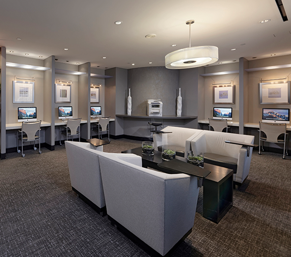 the business center at Aura Pentagon City with several computer stations, printer station and seating areas