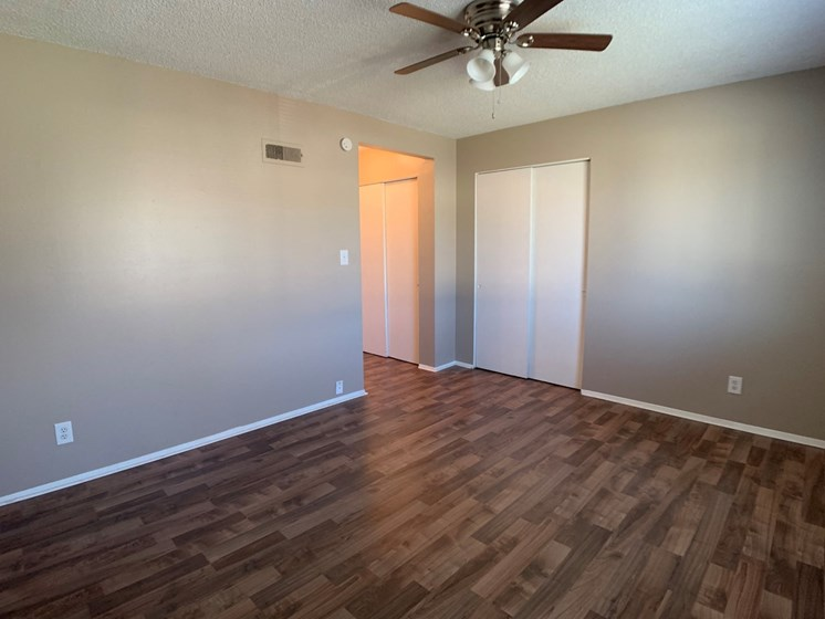 Large bedroom with ceiling fan and two closets