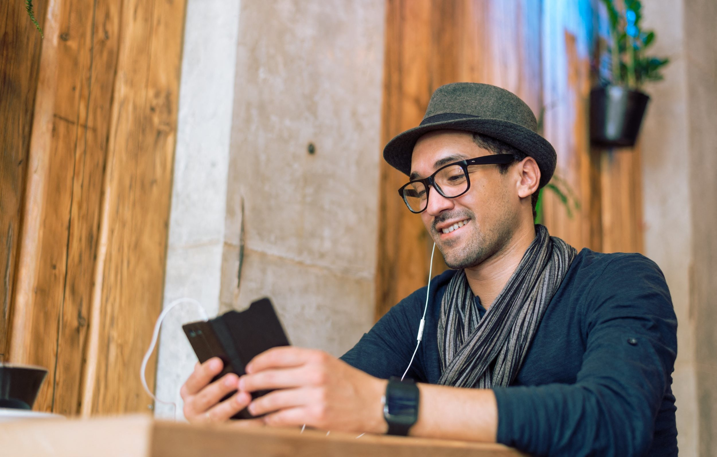Man Sitting At Table Looking at Smartphone
