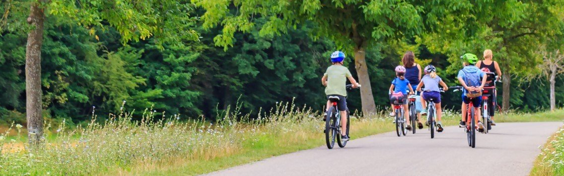 Family Riding Bicycles Down Grassy Path