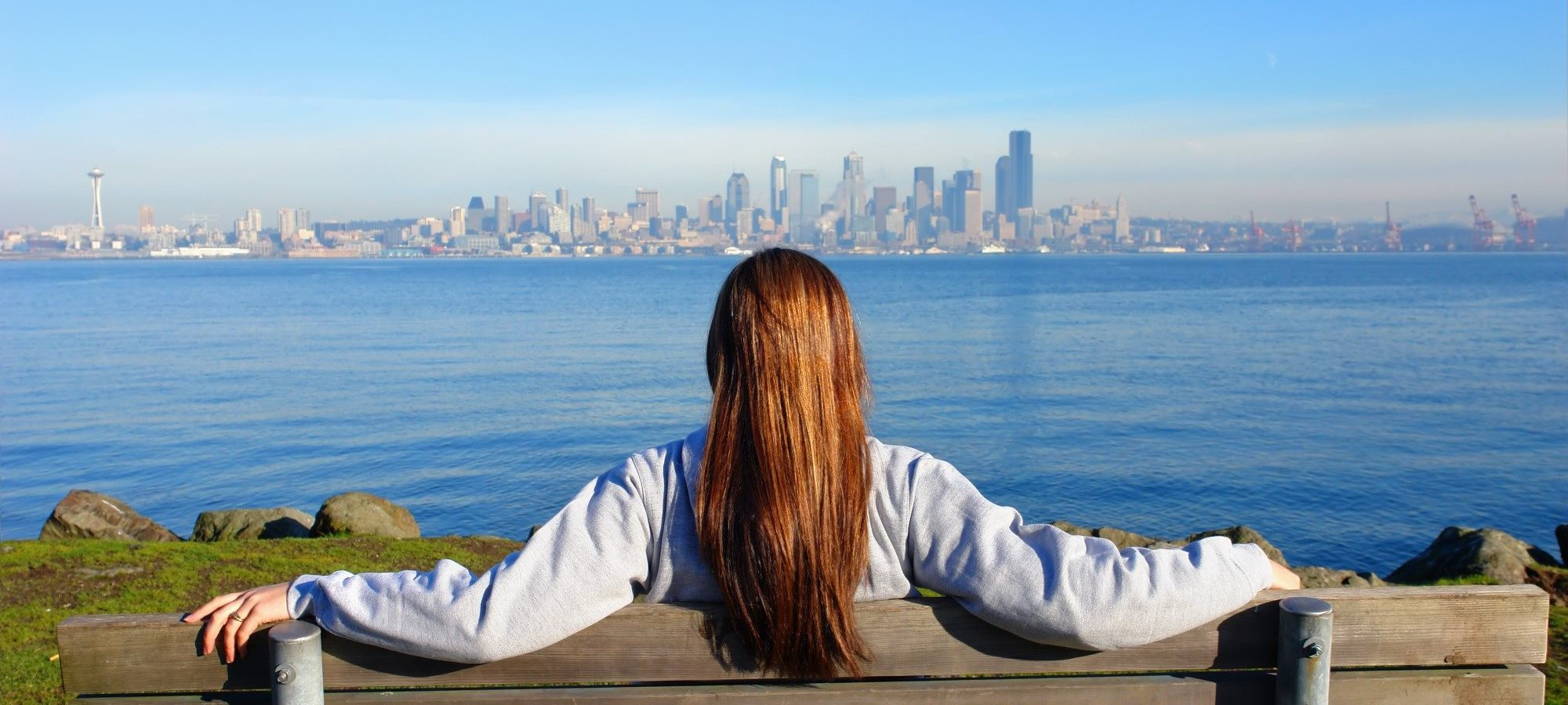 Woman Sitting on Bench Looking at Downtown Seattle, Washington Skyline