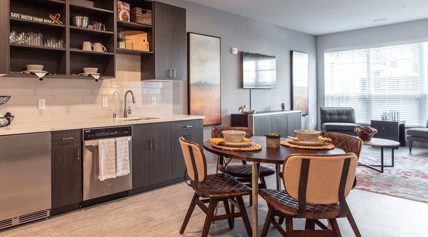 Kitchen with stainless steel appliances, dark cabinetry, and matching dining table in an apartment at Brookfield Reserve