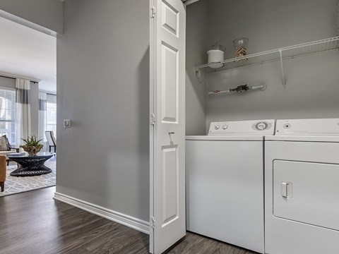 Full size washer and dryer  closet with accordion doors.