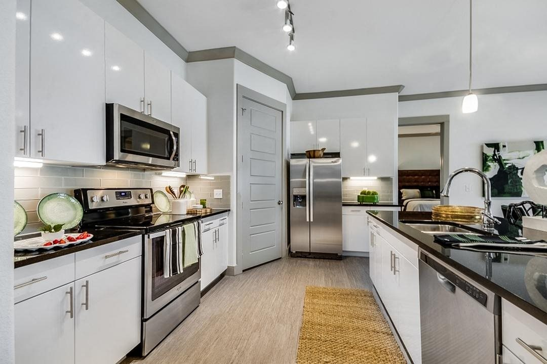 White Cabinetry And Appliances In Kitchen at Berkshire Spring Creek, Garland, Texas