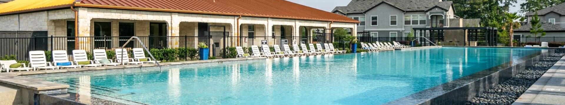 Swimming Pool With Lounge Chairs at Mansions Woodland, Conroe