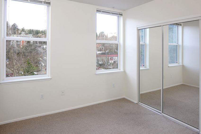 Bedroom with sliding glass closet doors Kitchen at Collins Circle Apartments in Portland OR