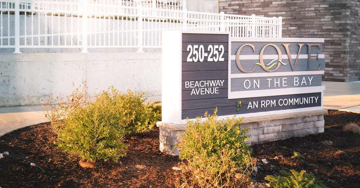 Exterior Sign with logo and address with plants in front of building
